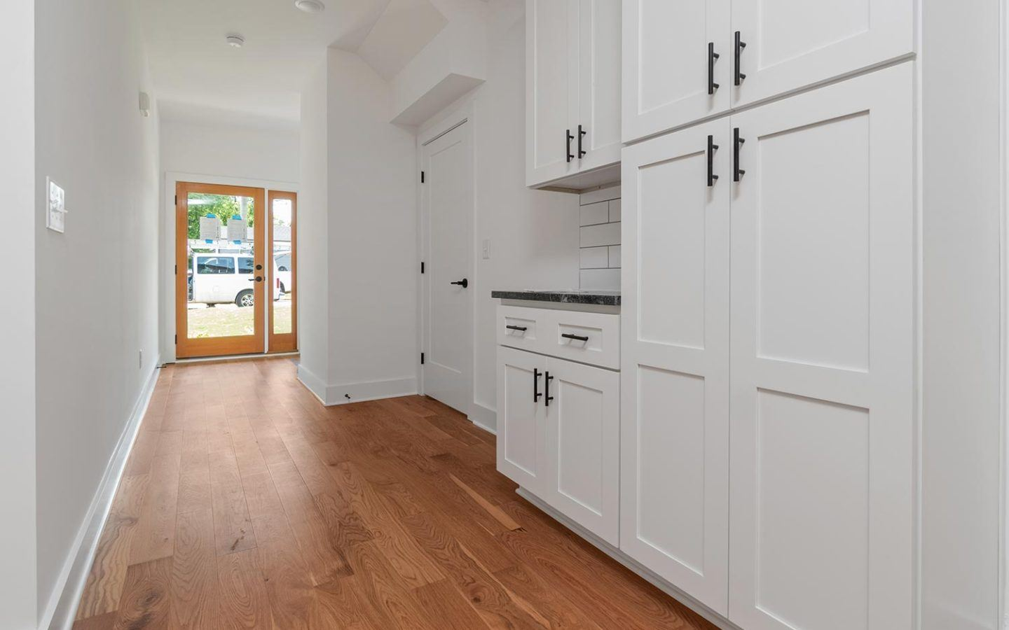 freshly painted kitchen cabinets in long bright hallway